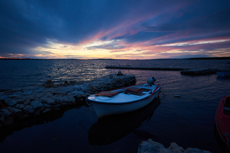 Beautiful summer seascape at sunset. Small boats anchored in sea inlet calm shallow water lit by red sun rays of setting sun. Tourism, fishing, diving, recreation and beauty of nature concept. 免版税图像