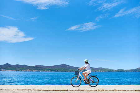 Girl cyclist in white summer closing and hat riding a bicycle along stony sidewalk on blue sparkling sea water and resort town at foot of mountains on opposite shore background. Tourism and vacations. 免版税图像