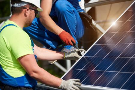 Due tecnici professionisti che collegano il pannello solare fotovoltaico alla piattaforma metallica utilizzando un cacciavite. Installazione del sistema di pannelli solari stand-alone, concetto di efficienza e professionalità.
