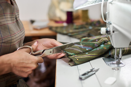 Close-up of female hands with scissors making marking cuts on pinned together garment details before sewing on electrical sewing machine. Handmade exclusive fashionable clothes creating process.