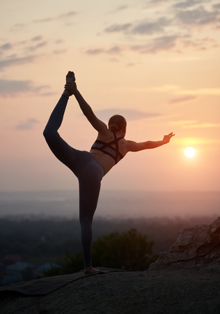 Back view of sportive flexible attractive girl in Natarajasana, or Lord of the Dance Yoga Pose outdoors on huge rock on copy space background of clear light pink summer sky at sunset. Stockfoto