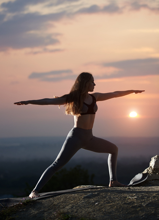 Slim attractive long-haired girl with stretched arms in standing yoga pose outdoors on big boulder on background of cloudy beautiful foggy pink sky and setting over horizon bright sun. Virabhadrasana