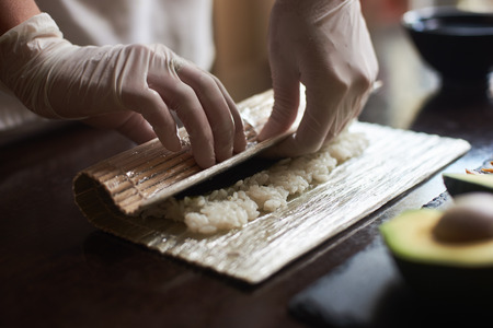 Master s hands making a sushi roll with nori, rice, cucumber and omelet using bamboo mat. Close-up view of process.