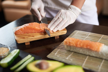 Close-up view of process of preparing delicious rolling sushi in restaurant. Female hands in disposable gloves slicing salmon.