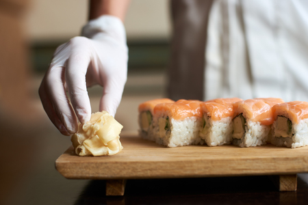 Close-up view of process of preparing delicious rolling sushi. Masters hand is holding ginger