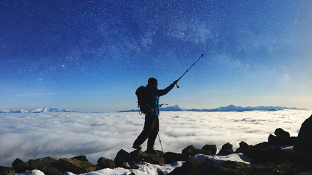Tourist hiker with backpack standing on huge rocks on the top of the mountain pointing with trekking pole at beautiful bright blue starry sky on background of foggy valley filled with white clouds. Banco de Imagens