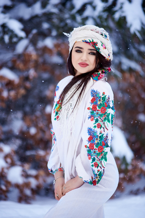 Portrait of attractive fashionable dark-haired woman in white dress embroidered with floral design, colorful kerchief in deep snow outdoors on spruce forest winter background.