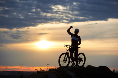 Sporty smiling man stands with bicycle on rock on top of a hill on a blurred background of a beautiful sunset. The man is dressed in sportswear and a helmet