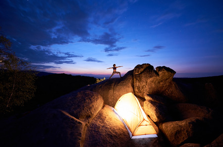 Camping on rock formation. Brightly lit tourist tent and silhouette of slim tourist girl doing yoga exercises on mountain top against dark blue sky at sunset. Sport, tourism concept. Virabhadrasana