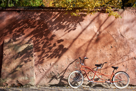 Modern comfortable orange tandem double bicycle with white wheels on paved empty sidewalk leaned against old plastered cracked red wall on bright sunny autumn day. Transport and traveling concept.