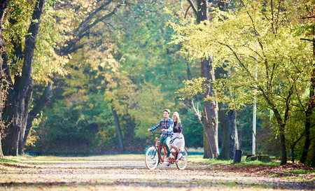 Young tourist couple, handsome bearded man and attractive blond long-haired woman cycling together tandem double bike by sunny alley with golden leaves on tall trees background in the fall