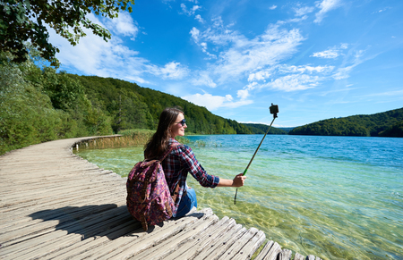 Colorful spring panorama of lit by bright sun green forest and clear blue lake. Young tourist woman in sunglasses and with backpack and camera sitting on wooden bridge enjoying beautiful view.