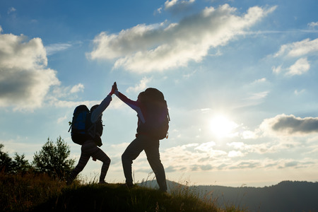 A cheerful couple with backpacks on top of the mountain give each other a high five against the background of the mountains and the cloudy sky with a bright sun at sunset. Bottom view