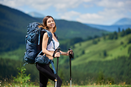 Portrait of attractive sporty female hiker with blue backpack and trekking poles, smiling on the top of a hill, enjoying summer day. Mountains, forests and cloudy sky on the blurred background