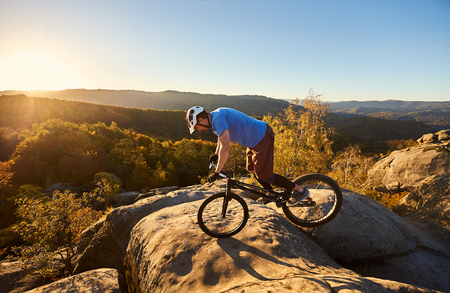 Courageous cyclist standing on front wheel on trial bicycle. Professional sportsman biker balancing on the edge of big boulder on the top of mountain at sunset. Concept of extreme sport