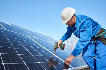 Man werknemer in blauw pak en beschermende helm installeren fotovoltaïsche zonnepaneel systeem met behulp van schroevendraaier. Professionele elektricien die blauwe zonnemodule monteert. Alternatieve energie ecologisch concept. Stockfoto