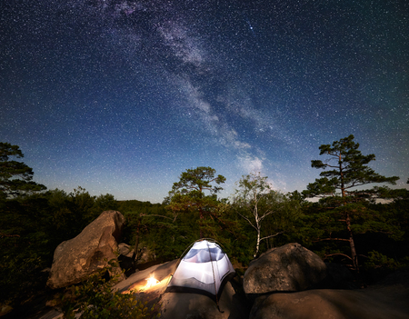Camping at summer night on rocky mountain. Illuminated tourist tent and bonfire under amazing night sky full of stars and Milky way. On the background beautiful starry sky, big boulders and trees