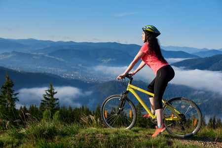 Happy young girl cyclist riding on yellow bicycle on a rural trail in the mountains, wearing helmet and red red t-shirt, enjoying morning haze in valley, forests on the blurred background. Copy space