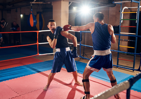 Male professional boxer training kick boxing with sparring partner in the ring at the sport club