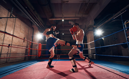 Two young men fighters exercising kickboxing in the ring at the health club Stock fotó