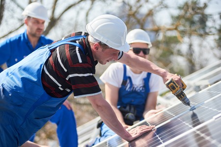Male team workers installing stand-alone solar photovoltaic panel system using screwdriver. Electricians mounting blue solar module on roof of modern house. Alternative energy ecological concept.
