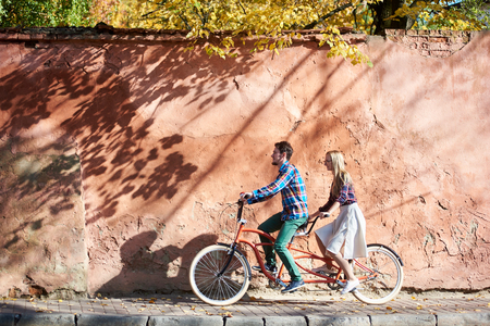 Young attractive happy tourist couple in casual clothing, bearded man and blond woman in glasses cycling together on double tandem bike on background of high red old crackled plastered wall. 版權商用圖片