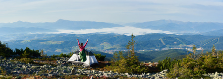 Panoramic view of camping on the top of mountain on bright summer morning. Back view of camper woman in pink sweater and sleeping bag standing in the entrance of tourist tent, holding hands lifting up