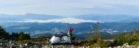 Panoramic view of camping on the top of mountain on summer morning. Back view of young hiker woman having a rest beside tourist tent, holding hands lifting up. On beautiful foggy mountains background.