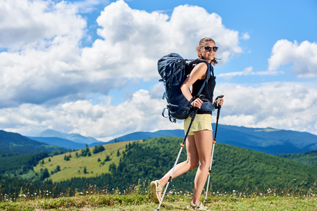 Attractive smiling woman tourist hiking mountain trail, walking on grassy hill, wearing backpack and sunglasses, using trekking sticks, enjoying summer sunny day in the Carpathian mountains
