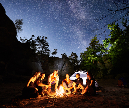 Happy Friends hikers having a rest together around campfire beside camp and illuminated tourist tent at night. On background beautiful night starry sky full of stars and Milky way, mountain rocks.