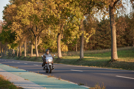 Bearded biker in sunglasses and black leather clothing riding modern powerful motorcycle along empty asphalt country road by beautiful tall trees with golden foliage on sunny autumn day. Stockfoto
