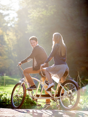 Young happy couple, bearded smiling man and blond long-haired attractive woman riding tandem double bicycle outdoors in summer park or forest on blurred sunny green trees foliage background. Stok Fotoğraf