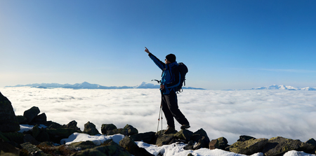 Tourist hiker with backpack and trekking poles standing on huge rocks pointing at bright blue sky on background of foggy valley filled with white clouds and distant mountain tops.
