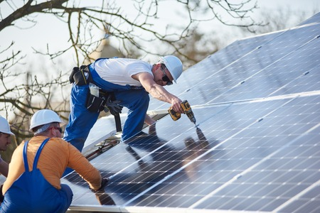 Male workers installing stand-alone solar photovoltaic panel system using screwdriver. Electricians mounting blue solar module on roof of modern house. Alternative energy ecological concept.