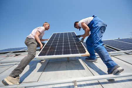 Male workers installing solar photovoltaic panel system. Electricians lifting blue solar module on roof of modern house. Alternative energy renewable concept.