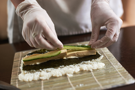 Close-up view of process of preparing rolling sushi with nori, rice, cucumber and omelet on bamboo mat