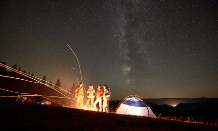 Night camping in the mountains near forest. Group of four friends hikers having a rest together around bonfire beside glowing tourist tent under beautiful night starry sky full of stars and Milky way. Stock Photo