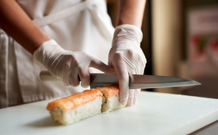 Closeup view of process of preparing rolling sushi. Chef is cutting roll on the white board