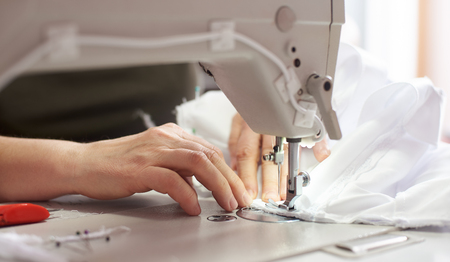 Female hands stitching white fabric on sewing machine at workplace with professional scissors on background. Seamstress hands holding textile for dress production. Blurred background. Close up view.