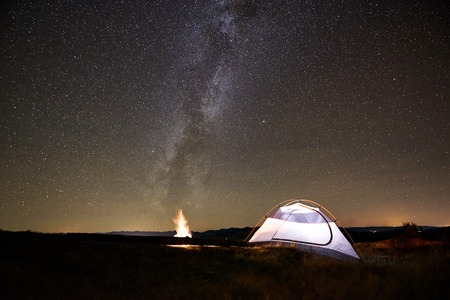 Tourist camping at summer night on the top of mountain. Glowing tent beside campfire under amazing night sky full of stars. On background starry sky and mountains. Tourism active lifestyle concept
