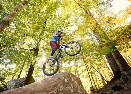 Professional cyclist balancing on back wheel on trial bike, man rider making acrobatic stunt on the edge of big boulder in the forest on summer sunny day. Concept of extreme sport active lifestyle Stok Fotoğraf