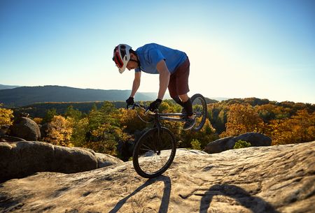 Professional cyclist riding on front wheel on trial bike. young Sportsman rider balancing on the edge of big boulder on the top of mountain at sunset. Concept of extreme sport active lifestyle