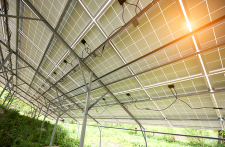 Interior of stand-alone photo voltaic solar system secured on metal rear legs on green grass, lit by summer sun. Alternative energy, environment protection and cheap electricity production concept.