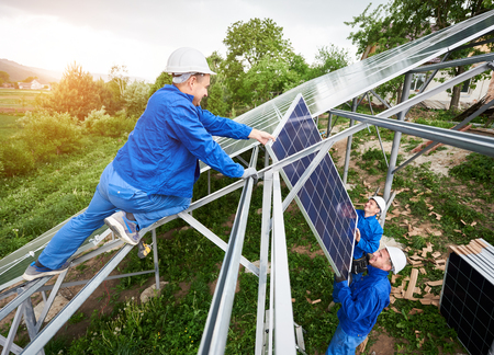 Installing of stand-alone solar photo voltaic panel system. Team of three technicians in hard-hats mounting the solar module on platform on green summer view background. Alternative energy concept.