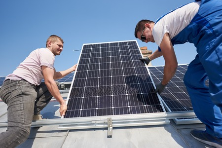 Male workers installing stand-alone solar photovoltaic panel system. Two electricians mounting blue solar module on roof of modern house. Alternative energy innovation ecology concept.