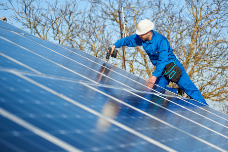 Man engineer in blue suit and protective helmet installing stand-alone solar photovoltaic panel system using screwdriver. Professional electrician mounting blue solar module on roof of modern house. Imagens