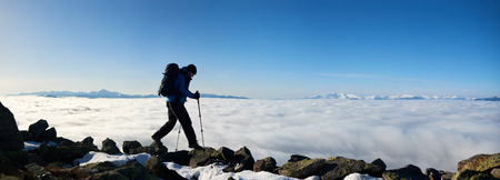 Hiker tourist man with backpack and hiker sticks hiking on the top of mountain on copy space background of blue sky at dawn, foggy valley filled with white clouds and distant snowy mountain tops. Stock fotó