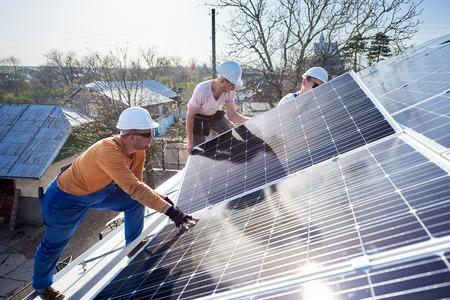 Mannelijke arbeiders die fotovoltaïsch zonnepaneelsysteem installeren. Elektriciens die blauwe zonnemodule op dak van modern huis monteren. Alternatieve energie ecologisch concept.