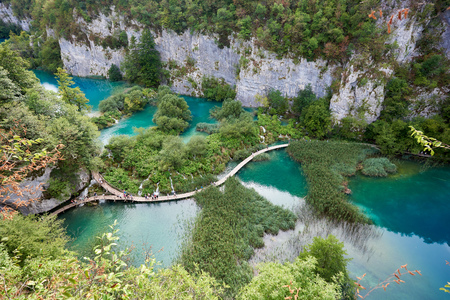 Plitvice Lakes National Park . Aerial view of lit by sun green forest on rocky cliffs and long wooden bridge with tourists over lakes with clear blue-green water.