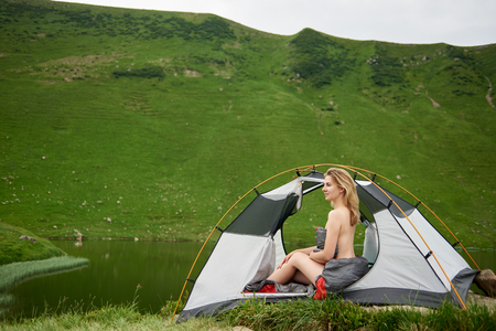 Side view of attractive woman hiker sitting in tent in sleeping bag, beautiful view of lake in the mountains on the background. Camping lifestyle concept adventure summer vacations outdoor